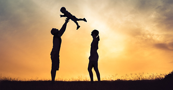 Couple playing with adopted baby in sunset