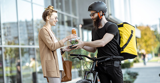 Man on bike delivering lunch to lady